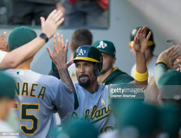 Marcus Semien of the Oakland Athletics is congratulated by teammates in the dugout after scoring a run on a double by Jed Lowrie of the Oakland...