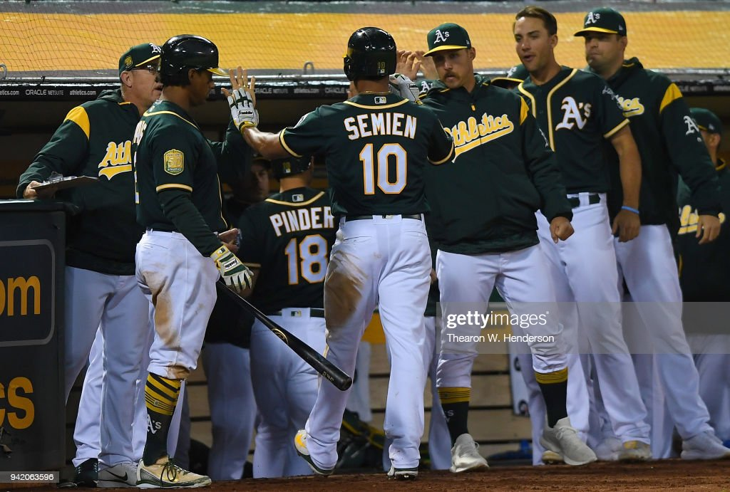 Marcus Semien #10 of the Oakland Athletics is congratulated by teammates after he hit a sacrifice fly scoring Chad Pinder #18 against the Texas Rangers in the bottom of the fourth inning at the Oakland Alameda Coliseum on April 4, 2018 in Oakland, California.