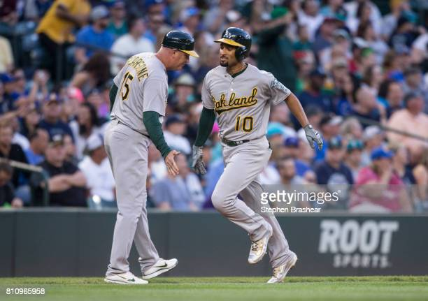 Marcus Semien of the Oakland Athletics is congratulated by third base coach Steve Scarsone as he rounds the bases after hitting a solo home run off...