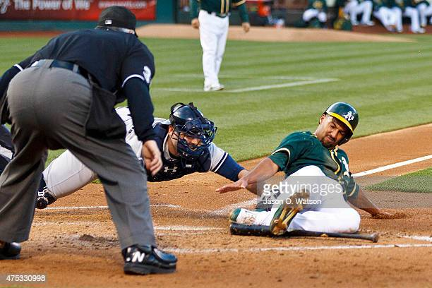 Marcus Semien of the Oakland Athletics is tagged out at home plate by Brian McCann of the New York Yankees in front of umpire Dana DeMuth during the...