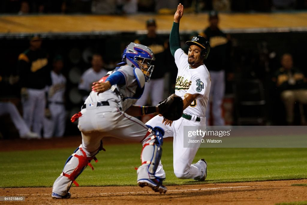 Marcus Semien #10 of the Oakland Athletics scores a run past Robinson Chirinos #61 of the Texas Rangers during the seventh inning at the Oakland Coliseum on April 2, 2018 in Oakland, California. The Oakland Athletics defeated the Texas Rangers 3-1.