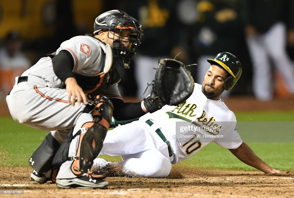Marcus Semien #10 of the Oakland Athletics scores sliding home before the throw to Welington Castillo #29 of the Baltimore Orioles in the bottom of the eighth inning at Oakland Alameda Coliseum on August 10, 2017 in Oakland, California. The Orioles won the game 7-2.