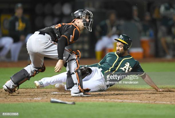 Marcus Semien of the Oakland Athletics scores sliding past catcher Caleb Joseph of the Baltimore Orioles in the bottom of the eighth inning at...