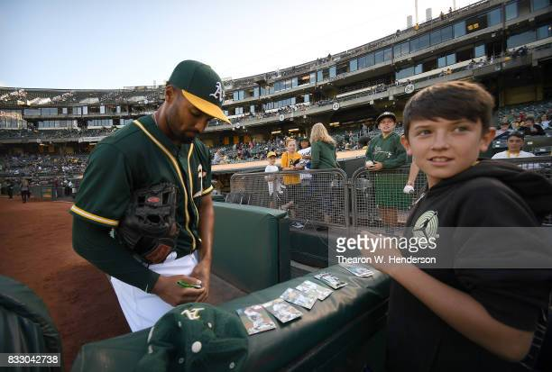 Marcus Semien of the Oakland Athletics signs an autograph for a fan prior to the start of their game against the Baltimore Orioles at Oakland Alameda...