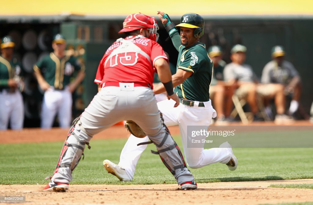 Marcus Semien #10 of the Oakland Athletics slides past Juan Graterol #13 of the Los Angeles Angels to score on a hit by Chad Pinder #18 in the fifth inning at Oakland Alameda Coliseum on September 6, 2017 in Oakland, California.