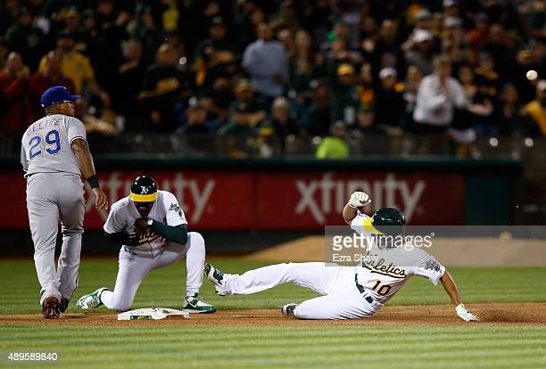 Marcus Semien of the Oakland Athletics slides safely in to third base for a triple that scored Jake Smolinski in the second inning against the Texas...