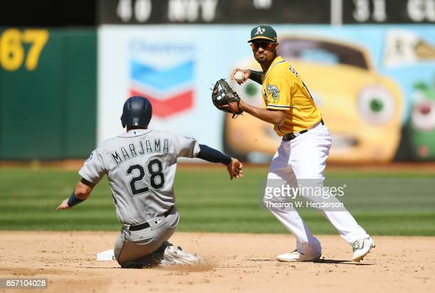 Marcus Semien of the Oakland Athletics throw to first base over the top of Mike Marjama of the Seattle Mariners in the top of the fifth inning at...