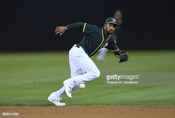 Marcus Semien of the Oakland Athletics watches as the ball gets past him for an rbi single off the bat of Chris Davis of the Baltimore Orioles in the...
