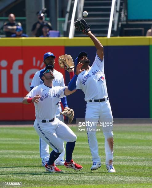 Marcus Semien of the Toronto Blue Jays makes a catch on a fly by Taylor Jones of the Houston Astros as Randal Grichuk runs into him during the...