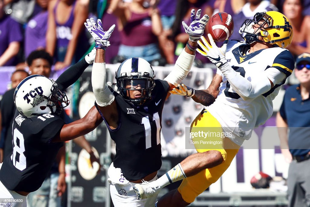 Marcus Simms #8 of the West Virginia Mountaineers bobbles a pass and gets a pass interference call against Nick Orr #18 of the TCU Horned Frogs and Ranthony Texada #11 of the TCU Horned Frogs in the first half at Amon G. Carter Stadium on October 7, 2017 in Fort Worth, Texas.