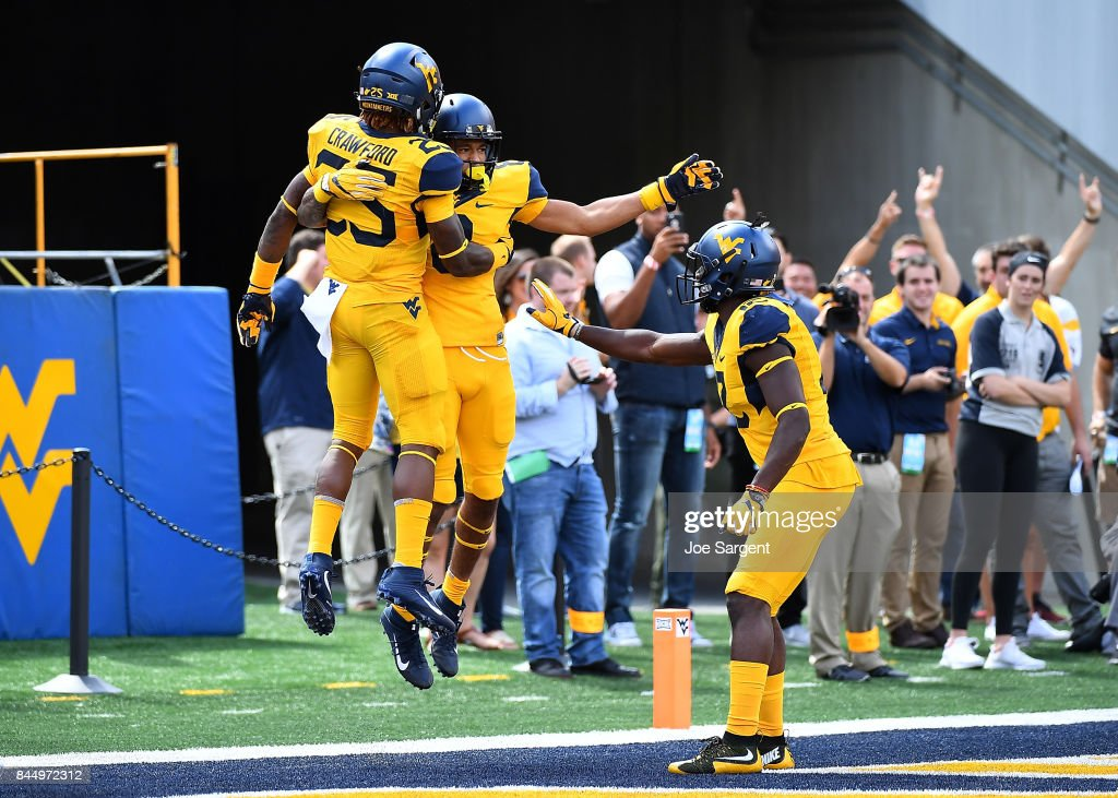 Marcus Simms #8 of the West Virginia Mountaineers celebrates his touchdown with teammates during the second quarter against the East Carolina Pirates at Mountaineer Field on September 9, 2017 in Morgantown, West Virginia. West Virginia won the game 56-20.