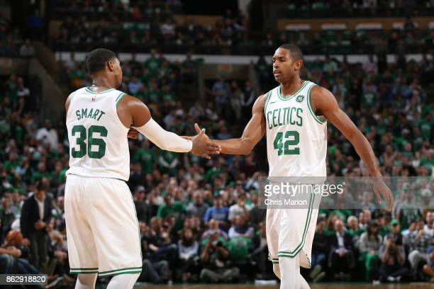 Marcus Smart and Al Horford of the Boston Celtics high five during the game against the Milwaukee Bucks on October 18 2017 at the TD Garden in Boston...