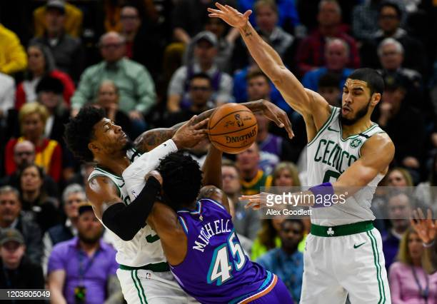 Marcus Smart and Jayson Tatum of the Boston Celtics guard Donovan Mitchell of the Utah Jazz during a game at Vivint Smart Home Arena on February 26...