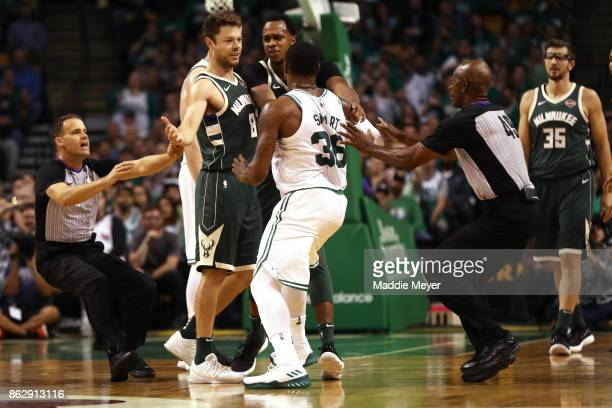 Marcus Smart of the Boston Celtics and Matthew Dellavedova of the Milwaukee Bucks exchange words during the second quarter at TD Garden on October 18...