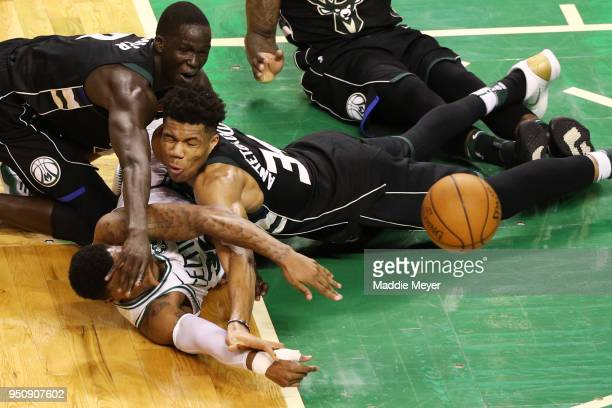 Marcus Smart of the Boston Celtics competes for a loose ball against Giannis Antetokounmpo of the Milwaukee Bucks and Thon Maker during the fourth...