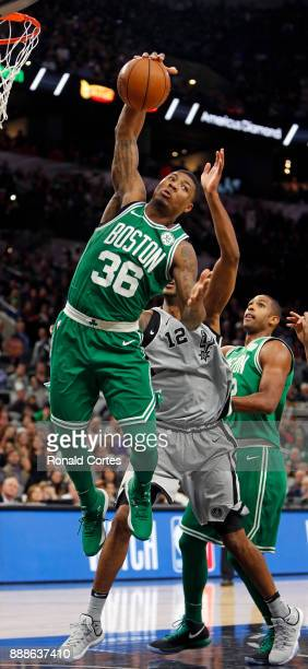 Marcus Smart of the Boston Celtics grabs a rebound in front of LaMarcus Aldridge of the San Antonio Spurs at ATT Center on December 08 2017 in San...