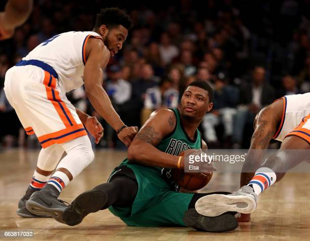 Marcus Smart of the Boston Celtics grabs the loose ball as Chasson Randle and Kyle O'Quinn of the New York Knicks defend at Madison Square Garden on...