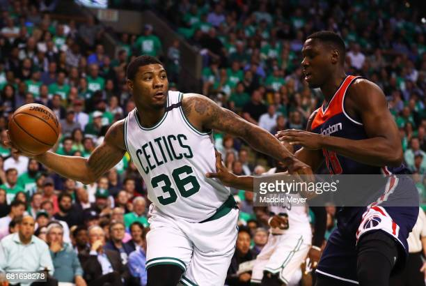 Marcus Smart of the Boston Celtics makes a pass around Ian Mahinmi of the Washington Wizards during the second half of Game Five of the Eastern...