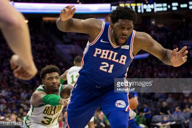 Marcus Smart of the Boston Celtics pushes Joel Embiid of the Philadelphia 76ers to the ground in the third quarter at the Wells Fargo Center on March...