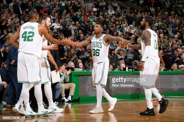 Marcus Smart of the Boston Celtics reacts with Al Horford and Kyrie Irving of the Boston Celtics on December 28 2017 at the TD Garden in Boston...