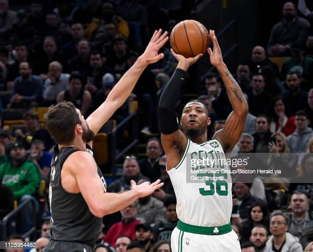 Marcus Smart of the Boston Celtics right shoots a three point basket over Joe Harris of the Brooklyn Nets during the first quarter of an NBA...