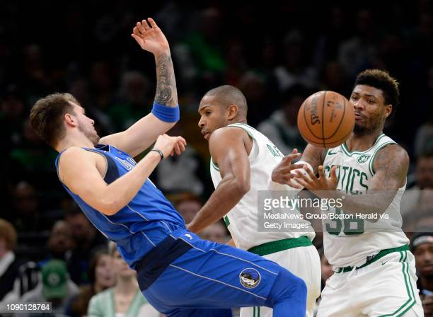 Marcus Smart of the Boston Celtics right takes control of a loose ball away from Luka Doncic of the Dallas Mavericks during the second half of an NBA...
