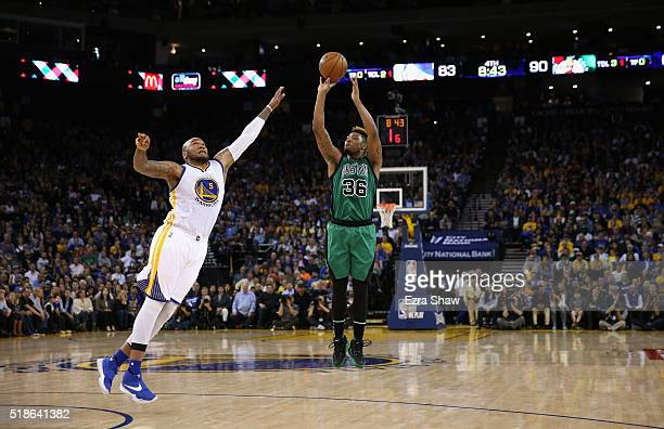 Marcus Smart of the Boston Celtics shoots over Marreese Speights of the Golden State Warriors at ORACLE Arena on April 1 2016 in Oakland California...