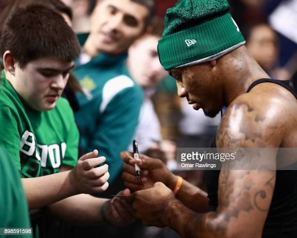 Marcus Smart of the Boston Celtics signs a fans ticket before the game against the Washington Wizards at TD Garden on December 25 2017 in Boston...