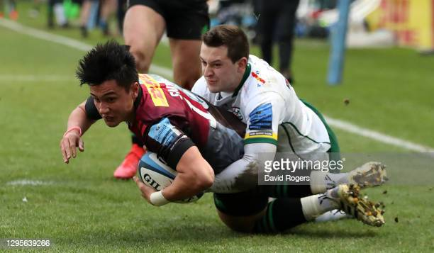 Marcus Smith of Harlequins dives over for their first try despite being held by Tom Parton during the Gallagher Premiership Rugby match between...