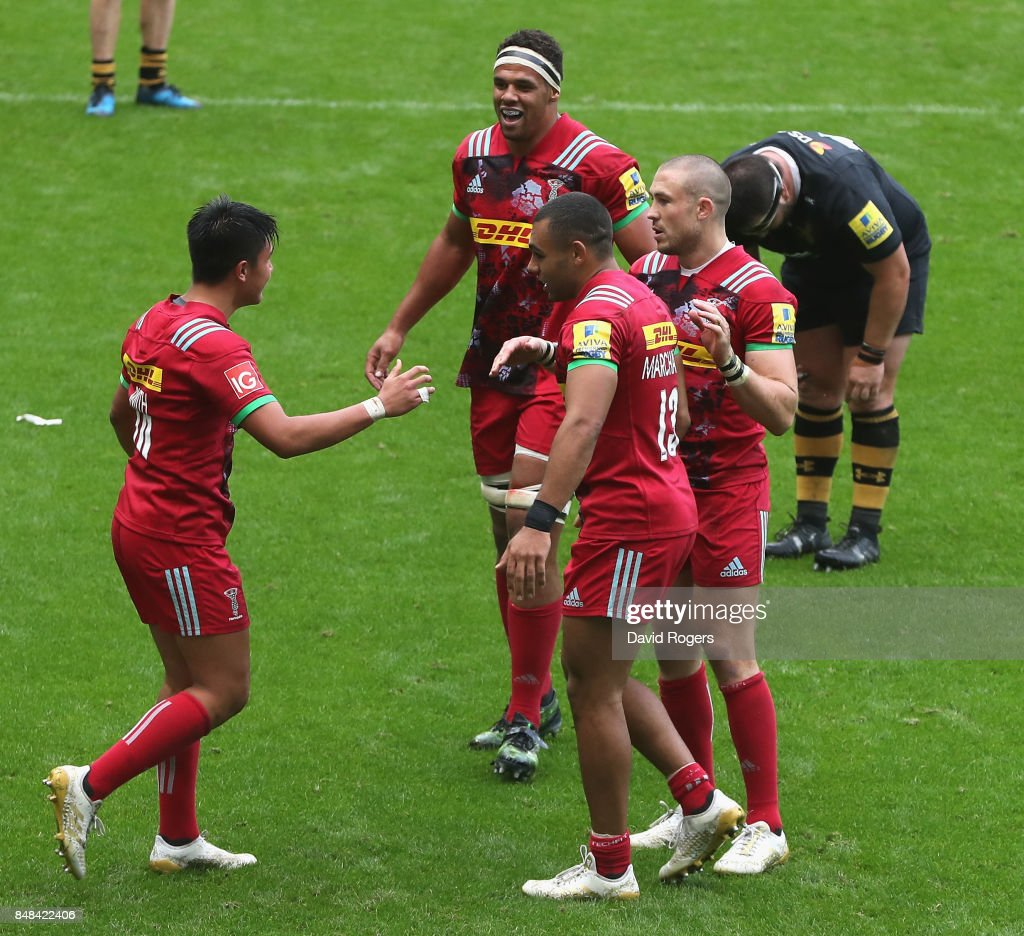Marcus Smith (L) of Harlequins is congratulated by team mates after their victory during the Aviva Premiership match between Wasps and Harlequins at The Ricoh Arena on September 17, 2017 in Coventry, England.