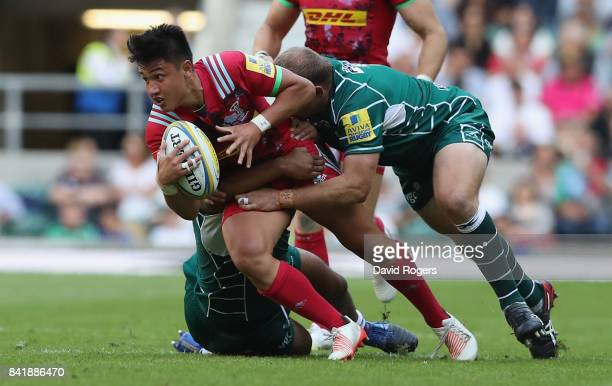 Marcus Smith of Harlequins is tackled by Danny HobbsAwoyemi and David Paice during the Aviva Premiership match between London Irish and Harlequins at...