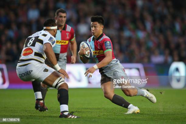 Marcus Smith of Harlequins takes on Victor Vito of La Rochelle during the European Rugby Champions Cup match between Harlequins and La Rochelle at...