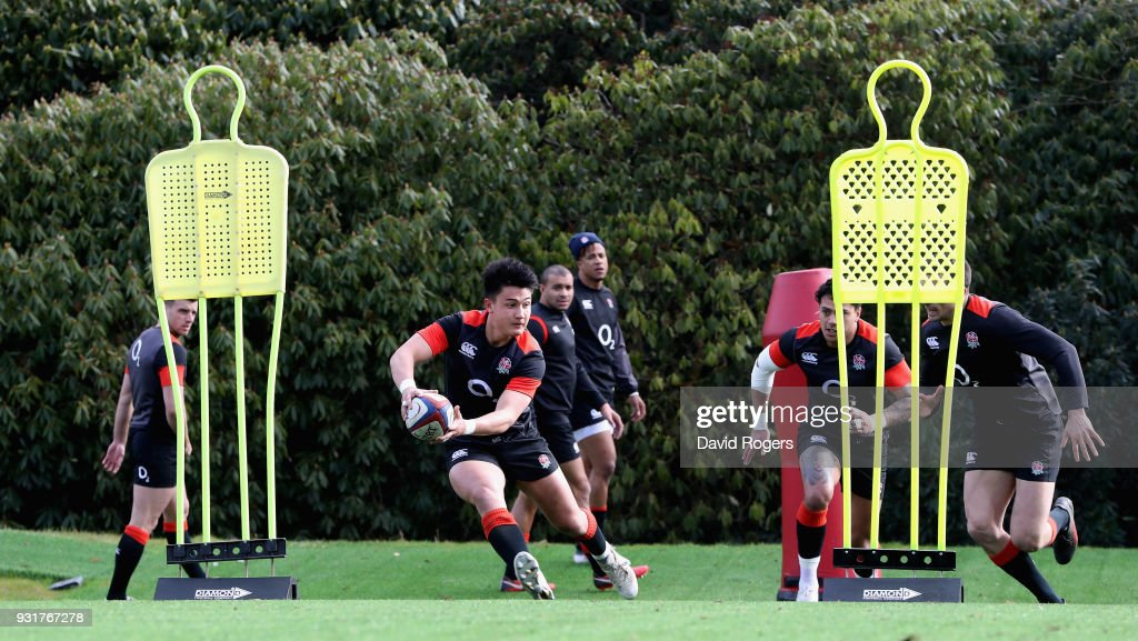 Marcus Smith (L) runs with the ball during the England training session held at Pennyhill Park on March 14, 2018 in Bagshot, England.