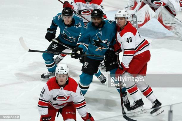 Marcus Sorensen and Joel Ward of the San Jose Sharks are defended by Victor Rask of the Carolina Hurricanes as Brock McGinn of the Carolina...