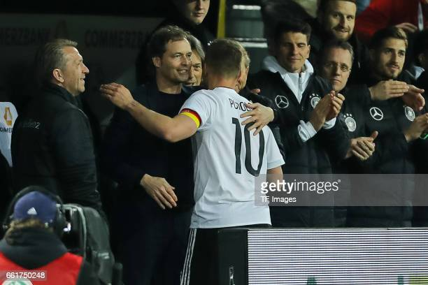 Marcus Sorg of Germany shakes hands with Lukas Podolski of Germany during the international friendly match between Germany and England at Signal...