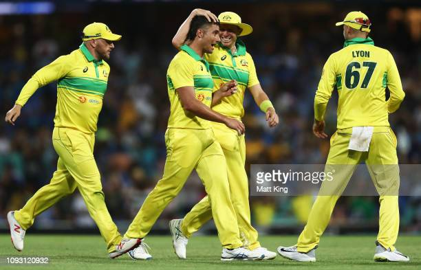 Marcus Stoinis of Australia celebrates with Peter Siddle after taking the wicket of Rohit Sharma of India during game one of the One Day...