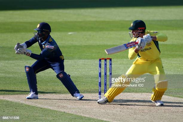 Marcus Stoinis of Australia hits out while Niroshan Dickwella of Sri Lanka looks on during the ICC Champions Trophy Warmup match between Australia...