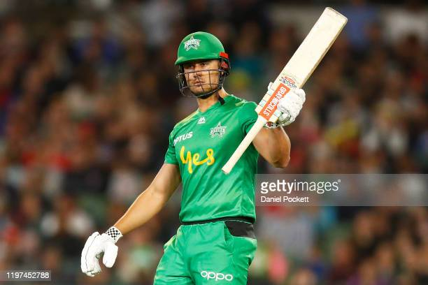 Marcus Stoinis of the Stars raises his bat after making fifty runs during the Big Bash League match between the Melbourne Stars and the Melbourne...