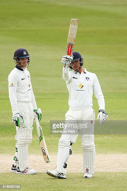 Marcus Stoinis of the VIC Bushrangers celebrates reaching 50 runs as teammate Peter Handscomb looks on during day 5 of the Sheffield Shield Final...