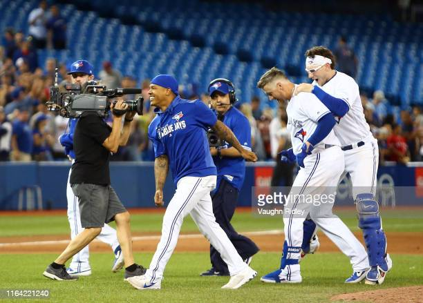Marcus Stroman and Danny Jansen of the Toronto Blue Jays celebrate with Justin Smoak after he hit a game winning RBI single in the tenth inning...