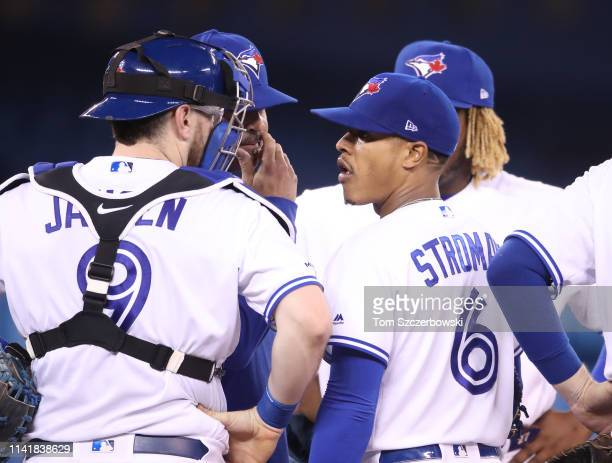 Marcus Stroman of the Toronto Blue Jays is visited on the mound by pitching coach Pete Walker as Danny Jansen listens in the fourth inning during MLB...