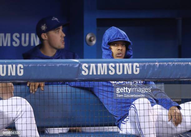 Marcus Stroman of the Toronto Blue Jays looks on from the top step of the dugout as Aaron Sanchez sits behind him during MLB game action against the...