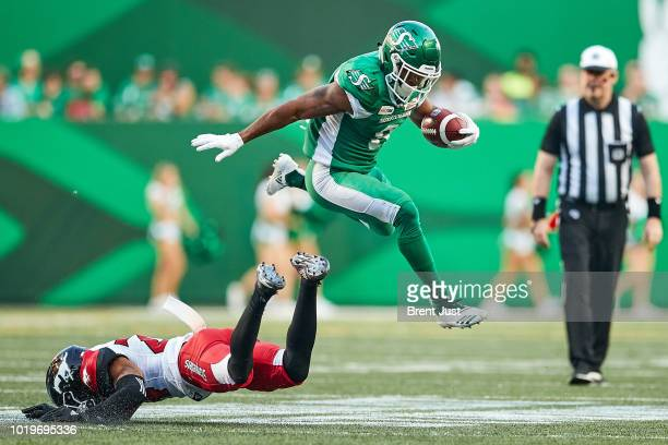 Marcus Thigpen of the Saskatchewan Roughriders leaps over a sprawling Tay GloverWright of the Calgary Stampeders in the game between the Calgary...