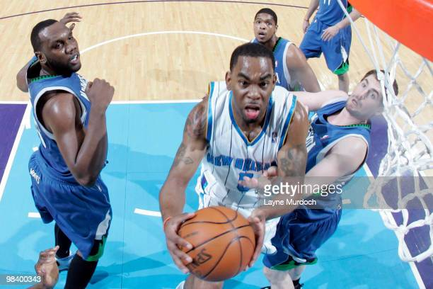 Marcus Thornton of the New Orleans Hornets shoots over Al Jefferson Ryan Gomes and Kevin Love of the Minnesota Timberwolves on April 11 2010 at the...