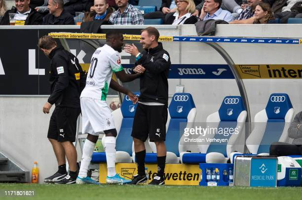 Marcus Thuram and Assistant Coach Alexander Zickler of Borussia Moenchengladbach are seen during the Bundesliga match between TSG 1899 Hoffenheim and...