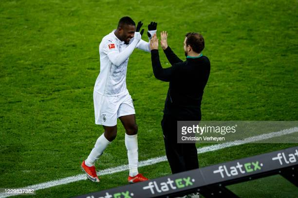 Marcus Thuram and Assistant Coach Rene Maric of Borussia Moenchengladbach celebrate after Marcus Thuram scored his teams third goal during the...