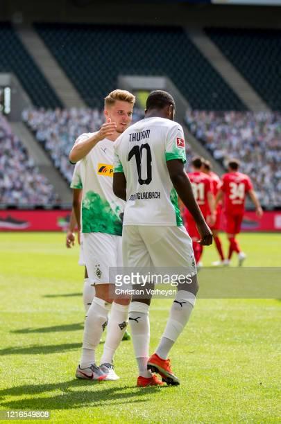 Marcus Thuram and Nico Elvedi of Borussia Moenchengladbach celebrate after their Teams fourth goal during the Bundesliga match between Borussia...