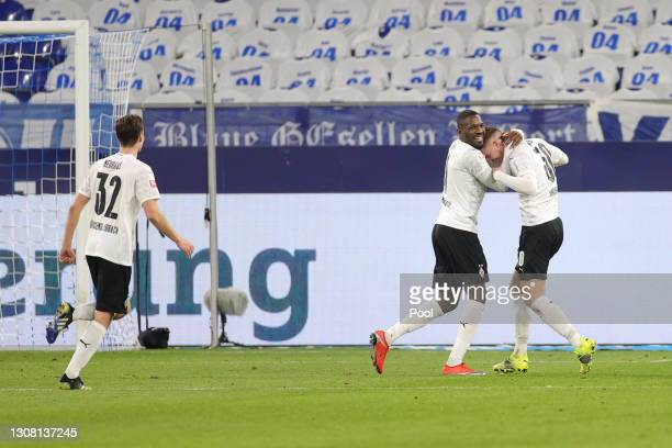 Marcus Thuram and Nico Elvedi of Borussia Moenchengladbach celebrate their side's third goal which was an own goal scored by Frederik Ronnow of FC...