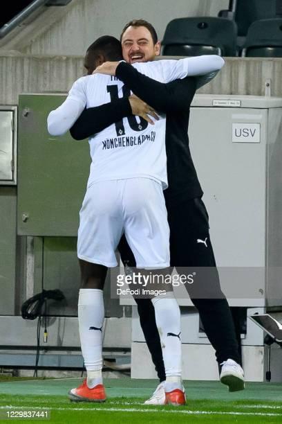 Marcus Thuram of Borussia Moenchengladbach and assistant coach Rene Maric of Borussia Moenchengladbach celebrates after scoring his team's third goal...