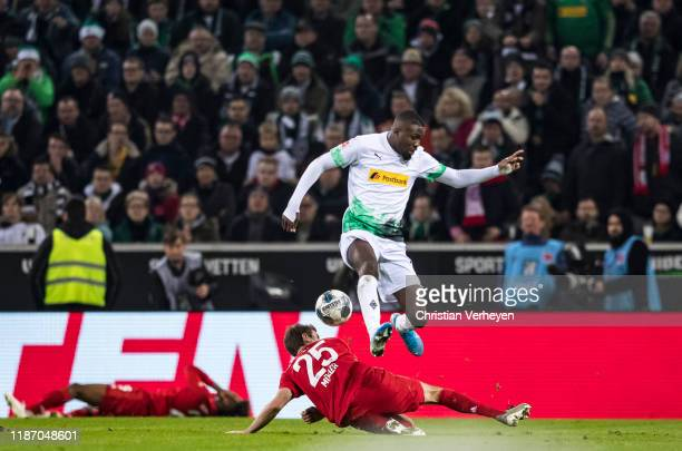 Marcus Thuram of Borussia Moenchengladbach and Thomas Mueller of Bayern Muenchen battle for the ball during the Bundesliga match between Borussia...